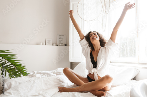 Obraz Image of pretty young woman wearing lingerie sitting in bed at home - fototapety do salonu