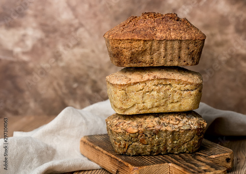 Fotobehang Brood Different kind of fresh bread, smooth stack, on wooden board, linen shelf, on table, content for bakery, space for text.