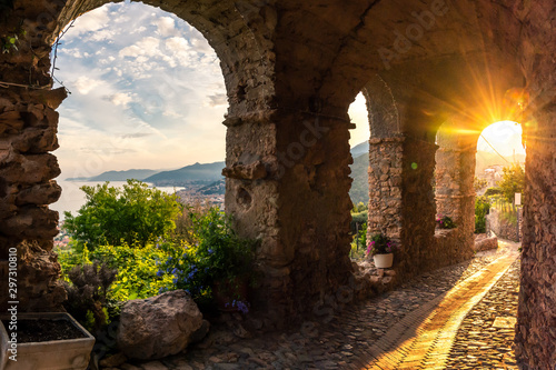 Fototapeta The sunset seen from an alley of the borough og Borgio Verezzi, Pietra Ligure, L