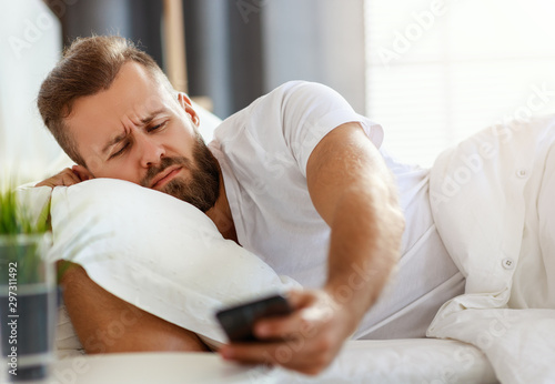 Obraz young bearded man wakes up in   morning in his bed with phone alarm clock. - fototapety do salonu