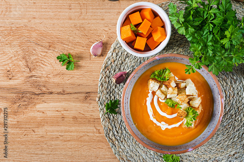 Pumpkin soup in a bowl served with parsley and croutons. Vegan soup. Thanksgiving day food. Halloween meal. Top view
