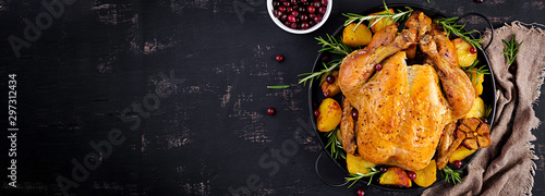 Baked turkey or chicken. The Christmas table is served with a turkey, decorated with bright tinsel. Fried chicken. Table setting. Christmas dinner. Banner. Top view - 297312434