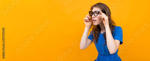a woman with glasses on a yellow background, a girl in a blue dress with poor ey Wallpaper Mural