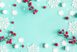 Fototapeta Kawa jest smaczna - Christmas or winter composition. Snowflakes and red berries on mint background. Christmas, winter, new year concept. Flat lay, top view, copy space