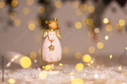 Decorative Christmas-themed figurines. Statuette of a Christmas angel. Christmas tree decoration. Festive decor, warm bokeh lights. - 297318074