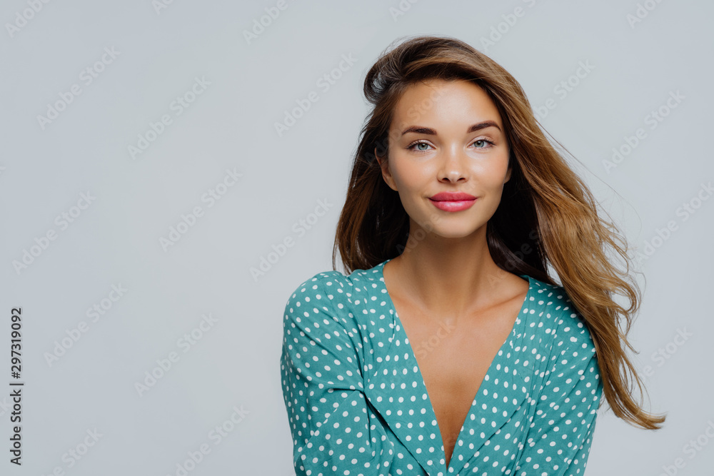 Fototapety, obrazy: Studio shot of positive young woman has long wavy hair, makeup, wears turquoise polkadot blouse, looks straightly at camera, models against white background, copy space for your advertisement