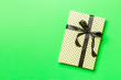 Leinwandbild Motiv Top view Christmas present box with black bow on green background with copy space