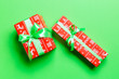 Leinwandbild Motiv wrapped Christmas or other holiday handmade present in paper with green ribbon on green background. Present box, decoration of gift on colored table, top view