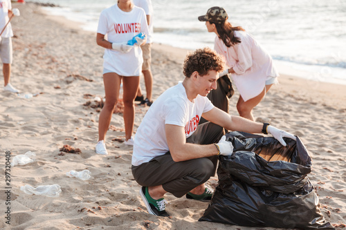 Vászonkép  Image of teenage volunteers cleaning beach from plastic with trash bags