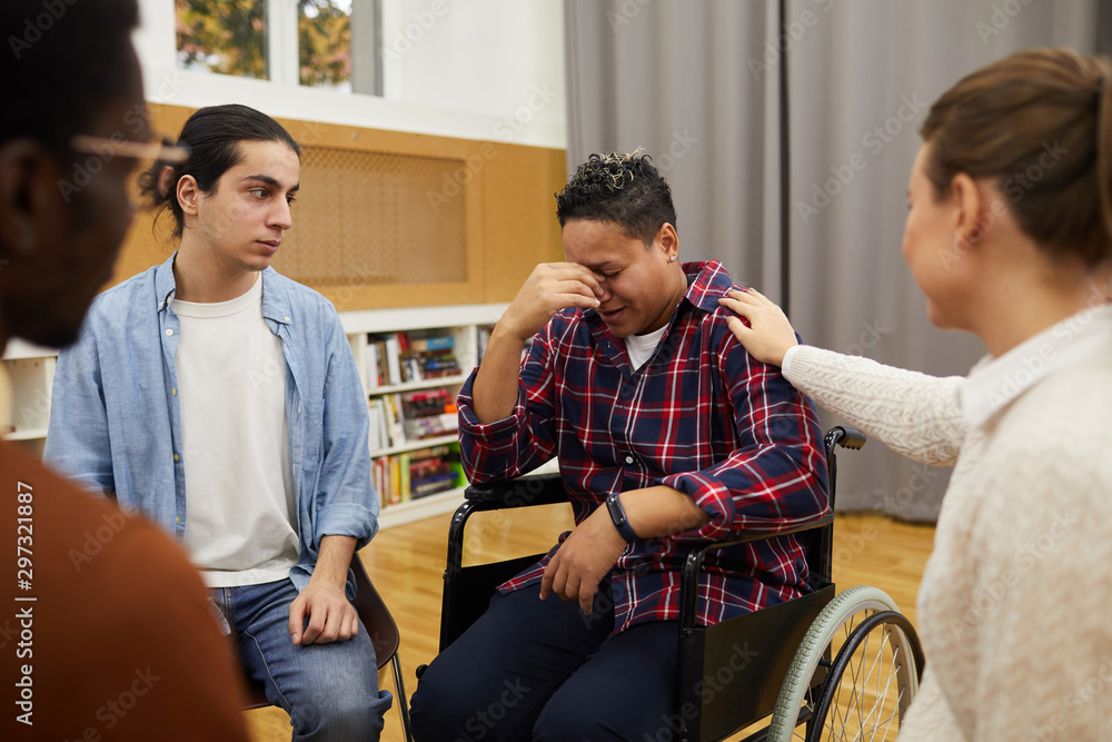 Fototapety, obrazy: Multi-ethnic group of people sitting in circle, focus on handicapped woman crying sitting in wheelchair during support meeting, copy space