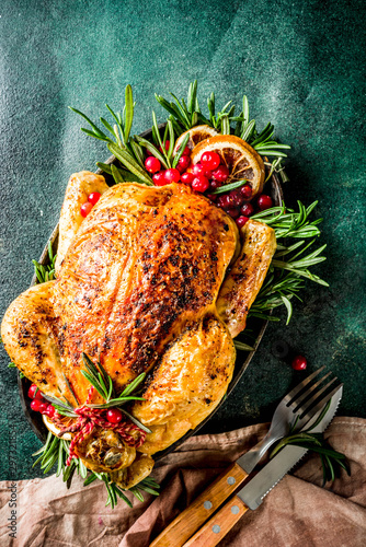 Fototapeta Traditional Christmas and Thanksgiving roasted whole chicken with fruit and rosemary. Dark green concrete table top view copy space obraz