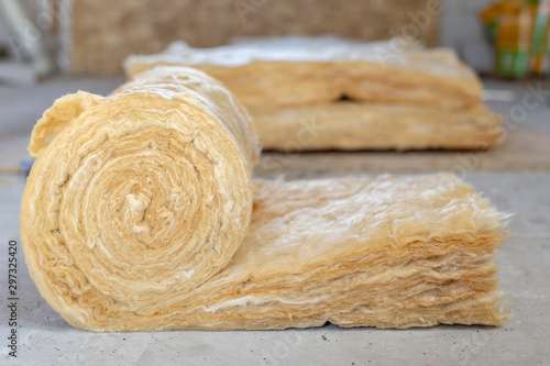 Obraz Mineral rockwool lying on attic floor inside house under construction - fototapety do salonu