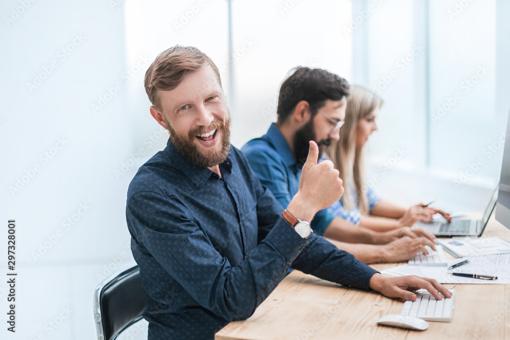 Fototapety, obrazy: successful business man sitting at his Desk and looking at the camera