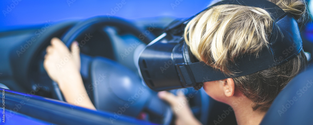 Fototapety, obrazy: Young male drive a car with virtual reality goggles. Boy sitting behind the steering wheel simulates driving a car with new tech devices. Learning road safety with vr headset. New technology concept