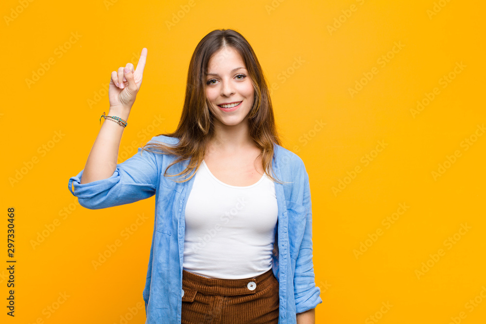 Fototapeta young pretty woman smiling cheerfully and happily, pointing upwards with one hand to copy space against orange wall