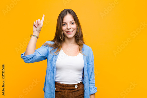 Obraz young pretty woman smiling cheerfully and happily, pointing upwards with one hand to copy space against orange wall - fototapety do salonu