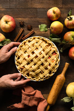 Homemade Apple Pie With Pastry Lattice On A Rustic Wooden Table Background. Hands Holding Apple Pie. Top View Vertical Orientation