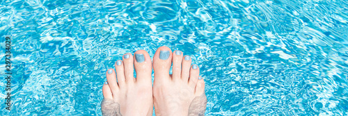 Female feet with glitter pedicure under clear pool water, banner.