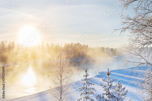 Wall Murals Forest river Mist over freezing river on a sunny cold winter day. Trees covered with frost and snow.