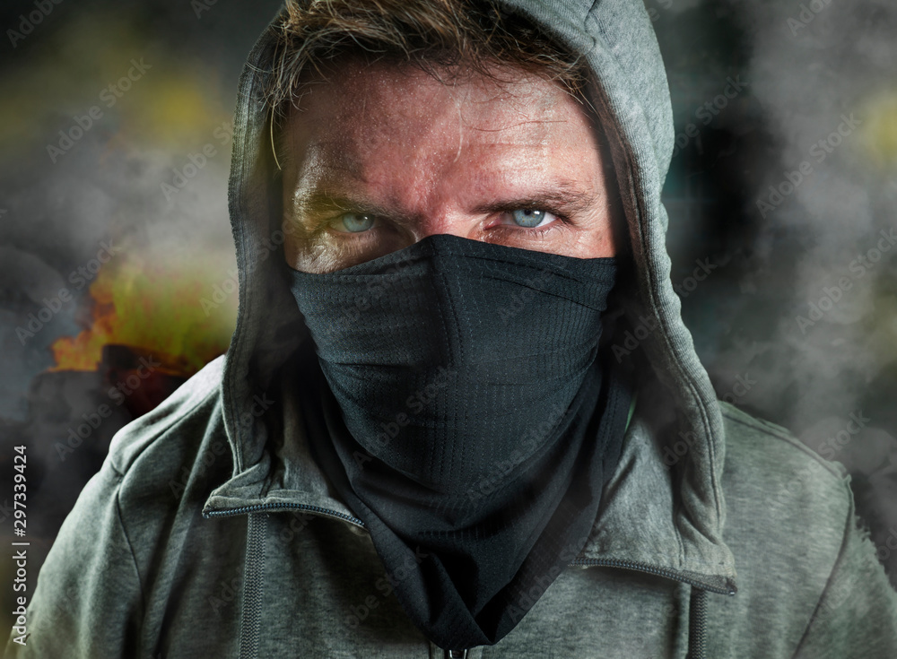 Fototapety, obrazy: young man as ultra and radical anarchist rioter . furious antifa protester in face mask hostile on street on demonstration in violet riot and chaos between fire and smoke