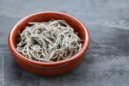 Fotomural Traditional Spanish food. Gulas with oil in ceramic dish.