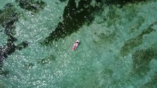 Top Down Aerial Footage Of A Couple Paddling On A Paddle Board On A Beach With Shallow Waters And Interesting Terrain In Indonesia 4K