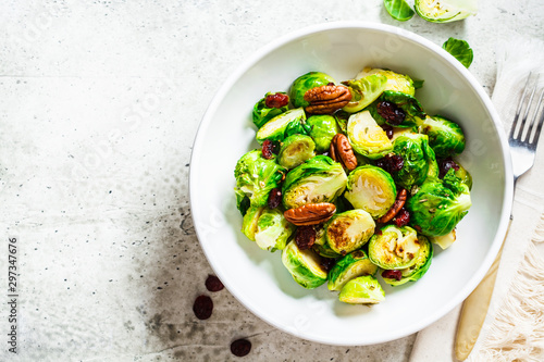 Bruxelles Roasted Brussels sprouts salad with cranberries and nuts in white bowl, top view. Healthy vegan food concept.