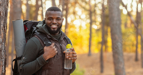Happy guy with backpack smiling over forest background Wallpaper Mural