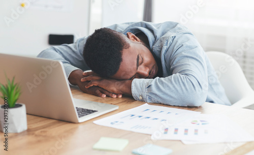 Obraz na plátně  Overworked african american employee sleeping at workplace in office