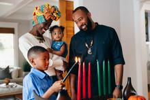 Boy Lights Candle To Celebrate Kwanzaa