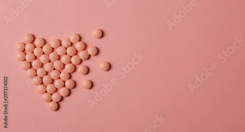 Fototapeta World Heart Day concept. Medical background. Pink Pills in form of heart on pink background. obraz