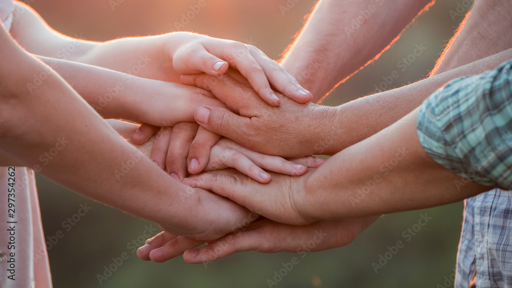 Fototapeta Friendly family put their hands on each other