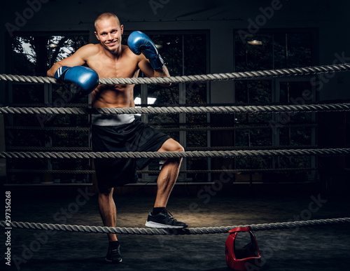 Smiling happy boxer is resting after sparring on the ring at dark gym Fototapet