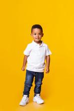 Cute Little Black Boy Standing In Studio Over Yellow Background