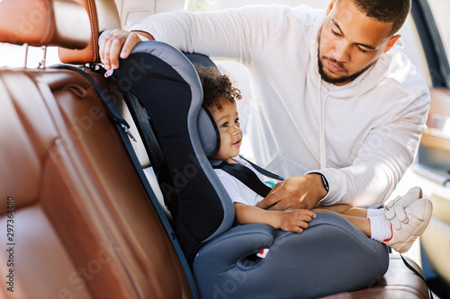 Side view of father fastening his little son safely in a car seat Wallpaper Mural