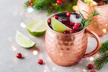 Christmas Moscow Mule Ice Cold Cocktail In Copper Cup With Cranberries, Lime And Rosemary On Stone Background.