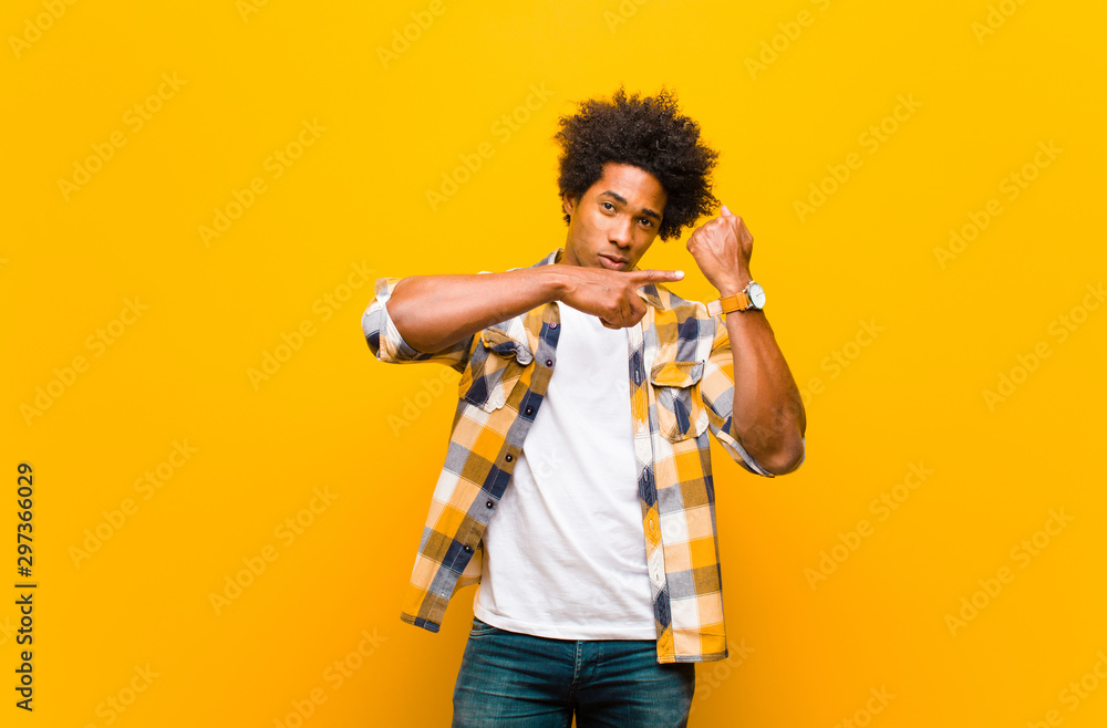 Fototapety, obrazy: young black man looking impatient and angry, pointing at watch, asking for punctuality, wants to be on time against orange wall
