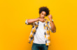 canvas print picture - young black man looking impatient and angry, pointing at watch, asking for punctuality, wants to be on time against orange wall
