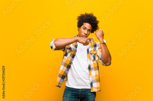 Pinturas sobre lienzo  young black man looking impatient and angry, pointing at watch, asking for punct