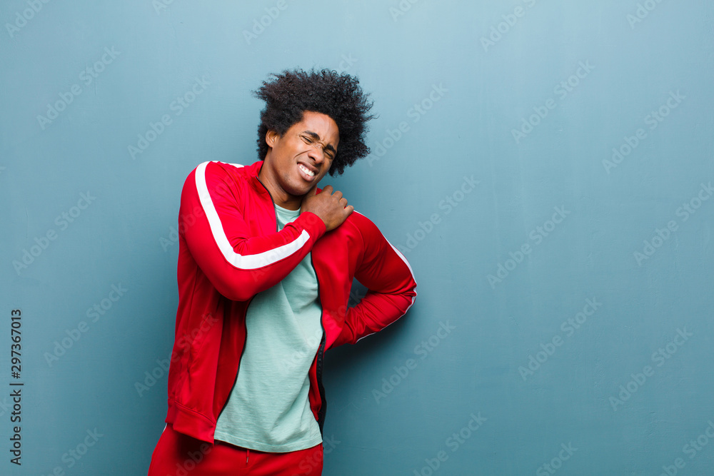 Fototapety, obrazy: young black sports man feeling tired, stressed, anxious, frustrated and depressed, suffering with back or neck pain against grunge wall