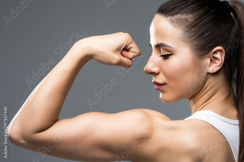 Stampa su Tela Portrait of a beautiful fitness woman showing her biceps isolated on gray backgr