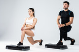 Athletic couple doing exercises over steps in aerobic class isolated on white background. Sport and health concept.