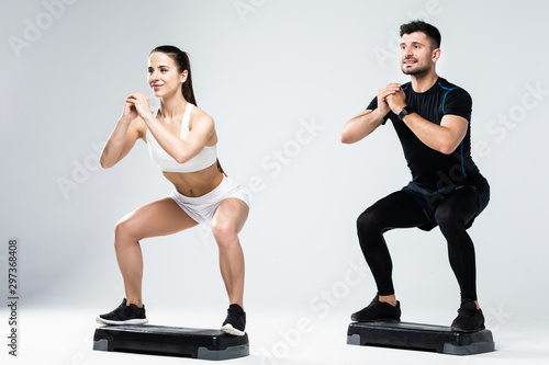 Fototapeta Athletic couple doing exercises over steps in aerobic class isolated on white background. Sport and health concept. obraz