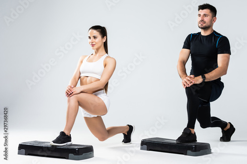 Athletic couple doing exercises over steps in aerobic class isolated on white background Canvas Print