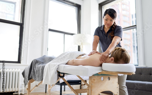 Poster Zen Chinese woman massage therapist giving a treatment to an attract