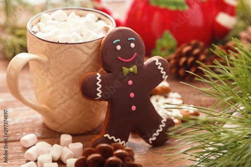 Foto auf Gartenposter Schokolade Gingerbread man and hot chocolate with marshmallows, on the background of Christmas tree branches on a wooden table