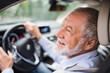 Leinwanddruck Bild - Close-up of happy senior man sitting in car in driver seat, driving.