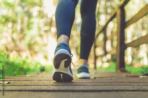 Obraz Woman runner feet walking in nature. Close up on shoes. Healthy lifestyle fitness concept. - fototapety do salonu