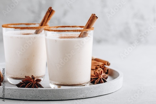 Fototapeta Homemade vanilla Christmas drink Eggnog in glass with grated nutmeg and cinnamon sticks obraz