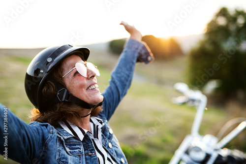 A cheerful senior woman traveller with motorbike in countryside. Tableau sur Toile